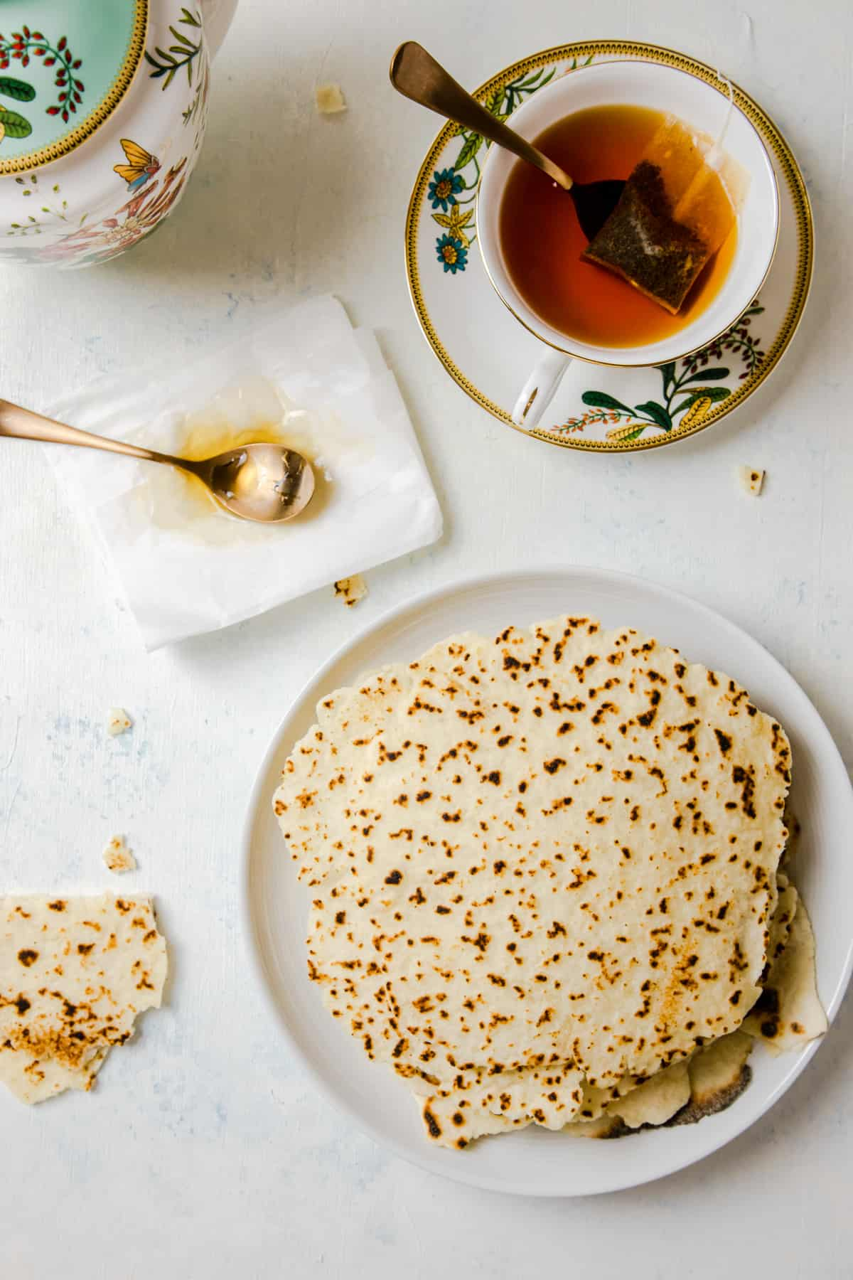 gluten-free flatbread top view surrounded by a tea cup and a tea pot.