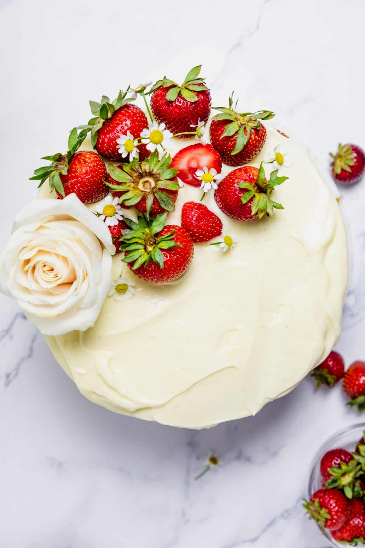 final strawberry jam cake decorated with a white rose, fresh strawberry and flowers.