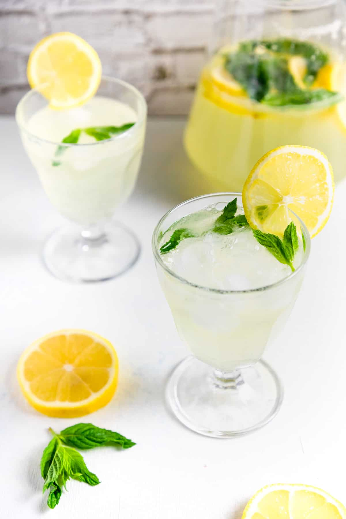 two cups of homemade lemonade with mint and ice.
