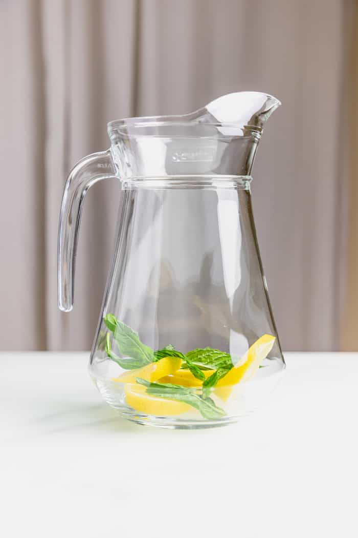 a flask with slices of lemon and some mint leaves