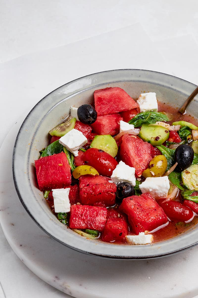 watermelon goat cheese salad in a gray bowl with a spoon.