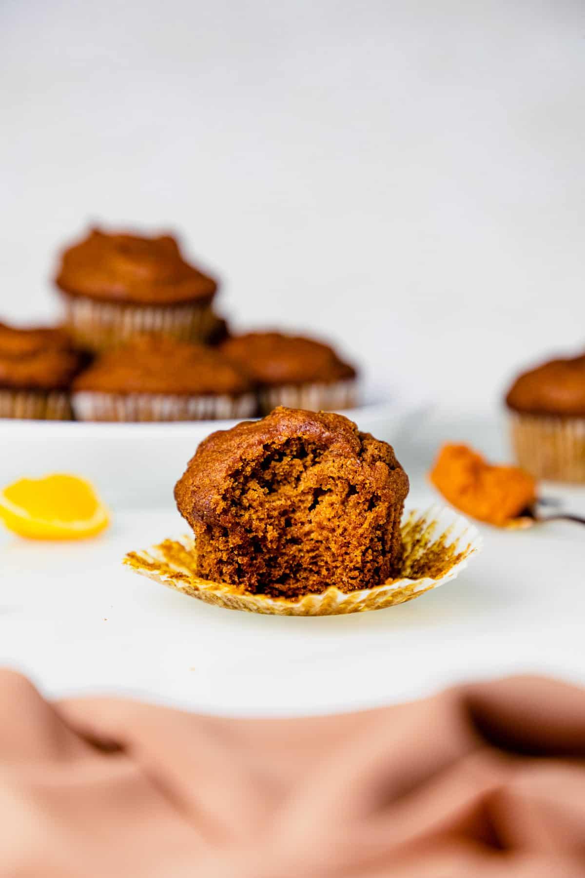 half eaten gluten free pumpkin muffin with a plate of gluten free pumpkin muffins in the background